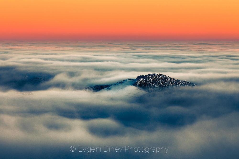 Самотен планински връх над облаците