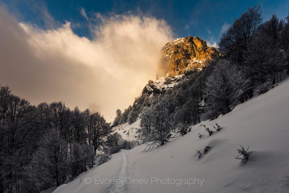 Облаци играят край огрян планински връх