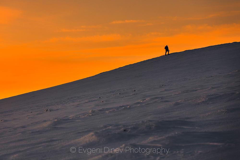 Планинар върви по заснежено старопланинско било по изгрев през зимата