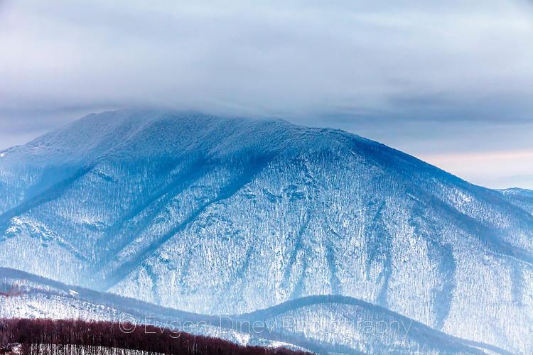 Снежен планински връх в облаците