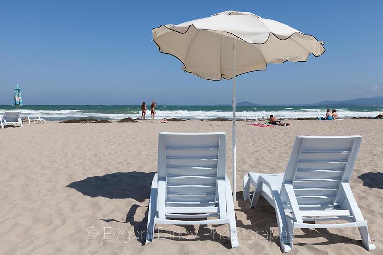 Шезлонг с чадър на плажа