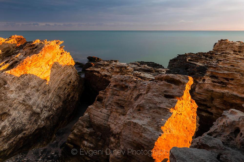 Морски скали огряни в златна светлина
