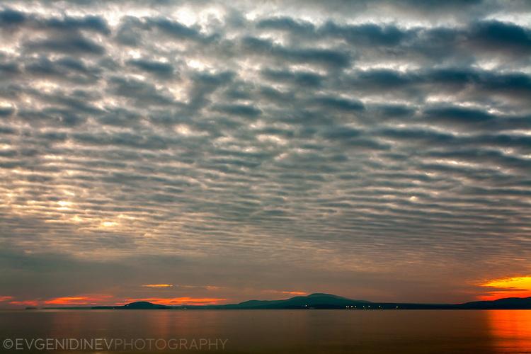 Заран край морето с перести облаци