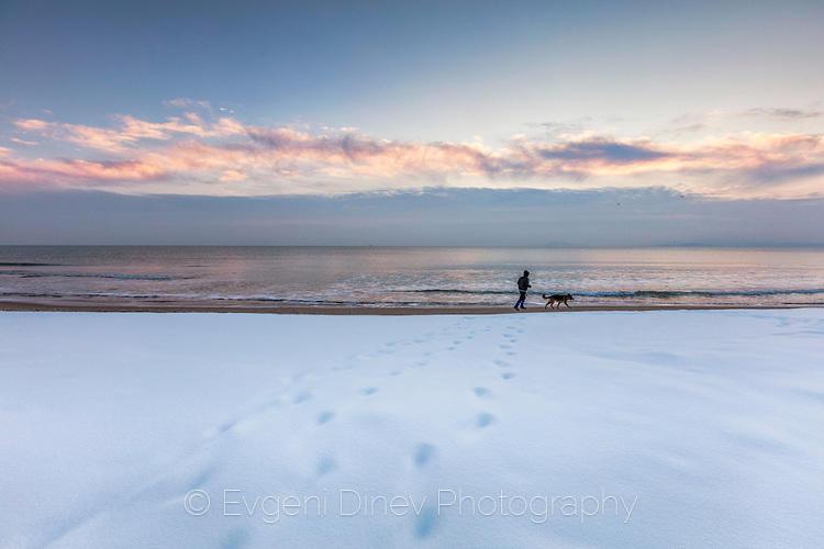 Човек с куче край плажа посред зима
