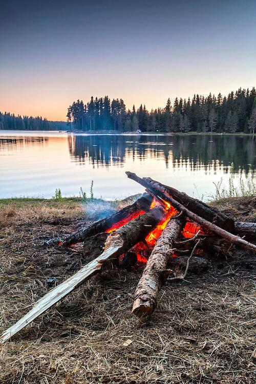 Огън край езерото по здрач