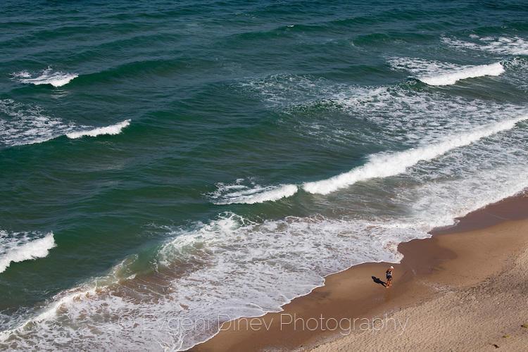 Мъж върви по безлюден плаж