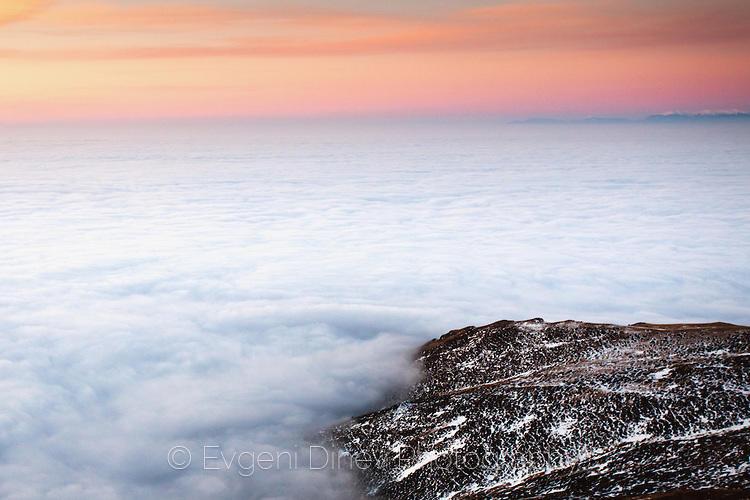 Къс земя в океан от облаци