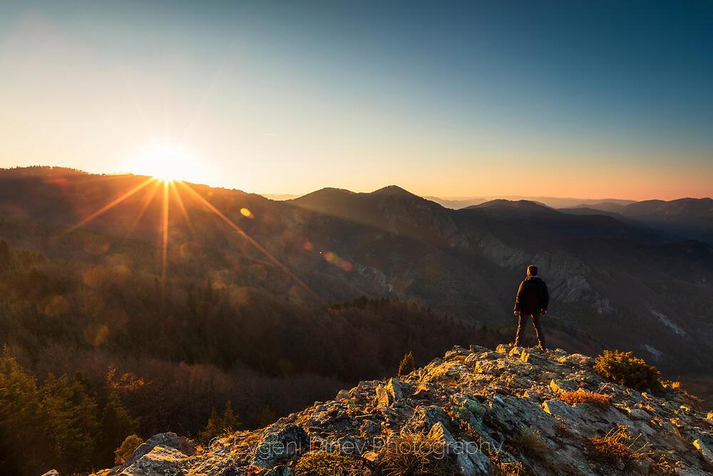 Човек на ръба на скала, загледан в залез над Родопите