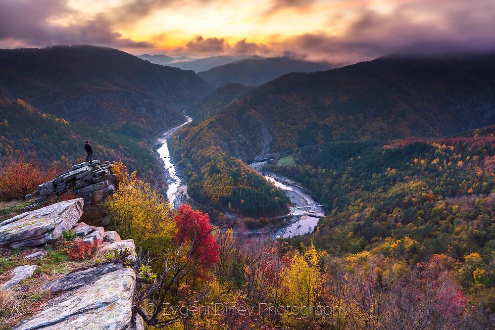 Човек застанал на скали надвиснали над река в планината