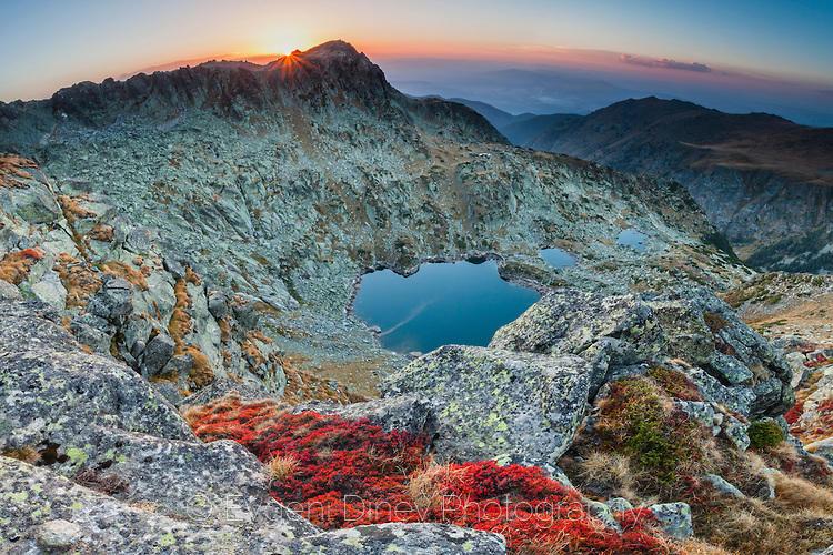 Панорама на планински върхове и езера по залез