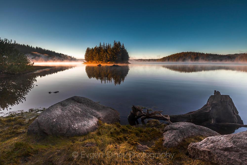 Разкошно островче насред езерото по заран, обвито в утринни пари