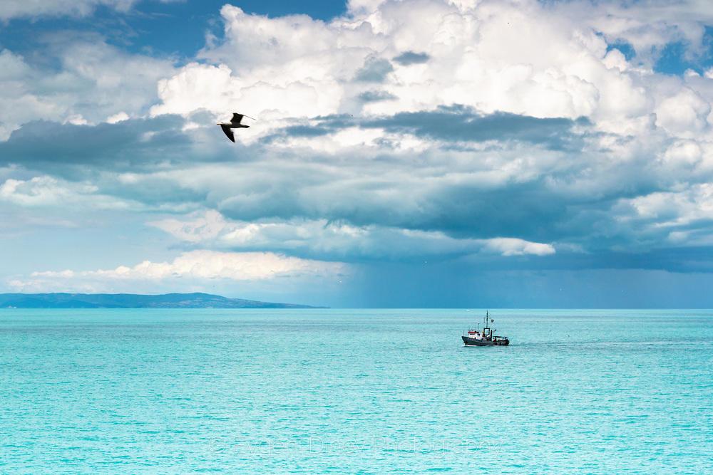 Рибарски кораб в синьото море и прелитащ гларус