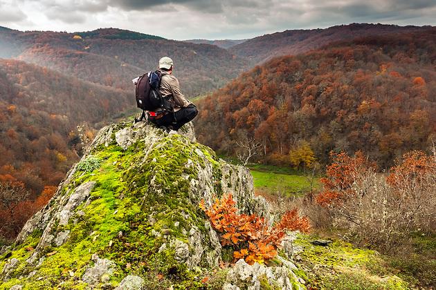 Турист седнал на скала в планината