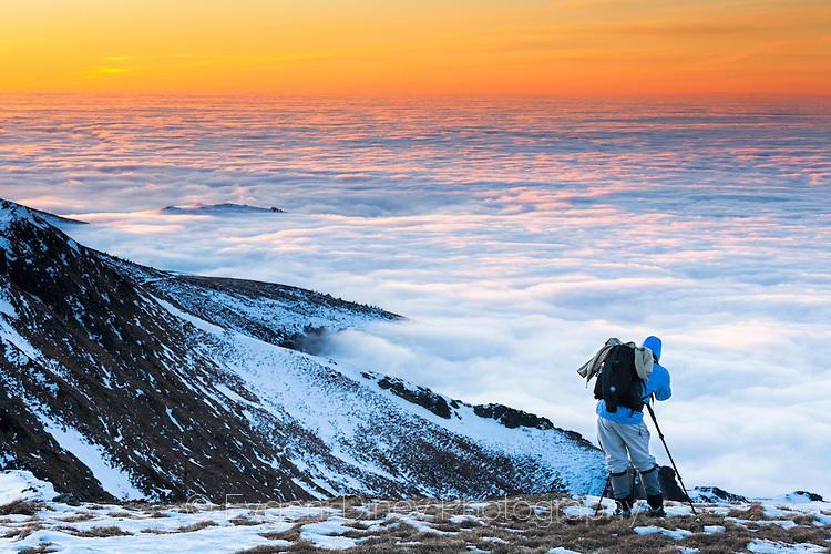 Фотограф снимащ планина над облаците